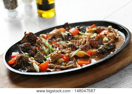 Tasty ragout with mushrooms in cast iron dish on wooden cutting board