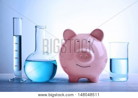 Pig money box and water in tubes on table. Saving water concept