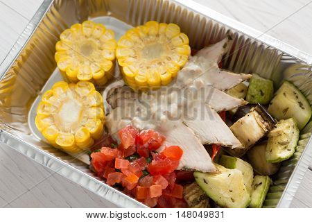 Healthy food delivery or take away, diet concept. Organic nutrition with protein, carb and fat balance. Weight loss dish in foil box. Vegetables, turkey and corn.