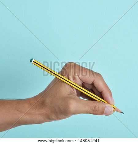 the hand of a left-handed man with a pencil, against a blue background