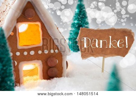 Gingerbread House In Snowy Scenery As Christmas Decoration. Trees And Candlelight For Romantic Atmosphere. Silver Background With Bokeh Effect. German Text Danke Means Thank You