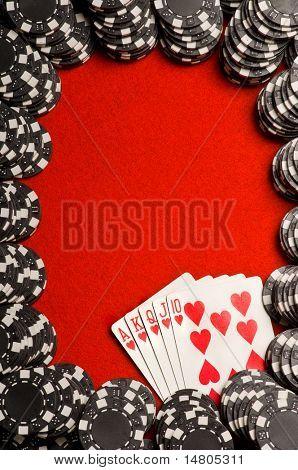 Black poker chips and a Royal Flush on red felt
