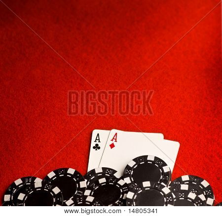 Pocket aces on red felt with black chips and room for copy space