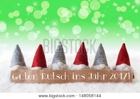 Label With German Text Guten Rutsch Ins Jahr 2017 Means Happy New Year 2017. Christmas Greeting Card With Gnomes. Sparkling Bokeh And Green Background With Snow And Stars.