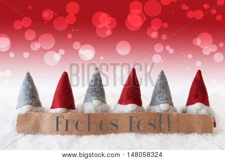Label With German Text Frohes Fest Means Merry Christmas. Christmas Greeting Card With Red Gnomes. Bokeh And Christmassy Background With Snow.