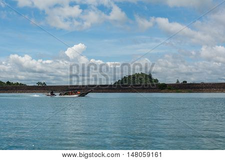 SURAT THANI THAILAND - MAY 31: Tourists sit in a boat in Ratchaprapha dam with beautiful green water and bright blue sky on May 31 2016 in Surat Thani Thailand.