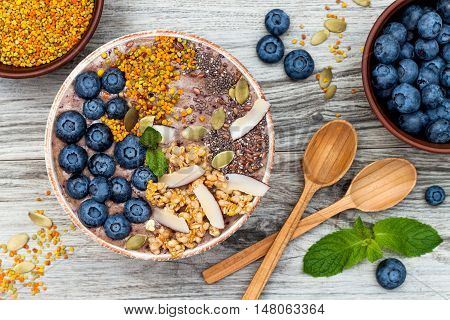 Acai breakfast superfoods smoothies bowl topped with chia flax and pumpkin seeds bee pollen granola coconut flakes and blueberries. Overhead top view flat lay