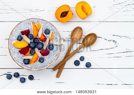 Detox and healthy superfoods breakfast bowl concept. Vegan coconut milk chia seeds pudding over rustic table with various fruits and blueberries. Overhead top view flat lay.