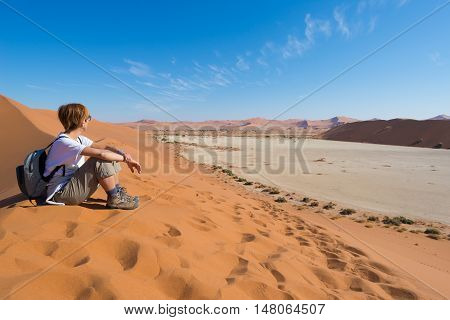 Relaxed tourist sitting on sand dunes and looking at the stunning view in Sossusvlei Namib desert best travel destination in Namibia Africa. Concept of adventure and traveling people.Relaxed tourist sitting on sand dunes and looking at the stunning view i