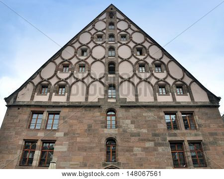 Nuremberg, Germany - April 12, 2015: Historic building in Nuremberg, Germany. The front facade of stone blocks with round decorative elements and with a pitched roof. Lookup.
