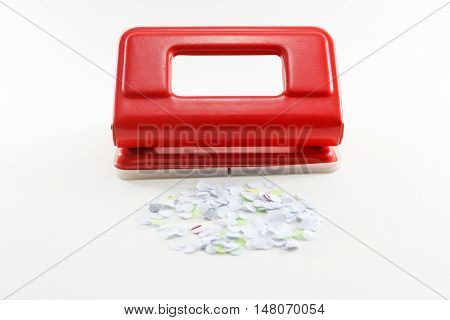 Red puncher and paper on white background isolated.