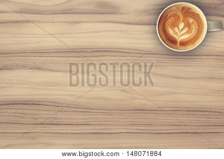 Coffee cup top view on teak wood texture background.