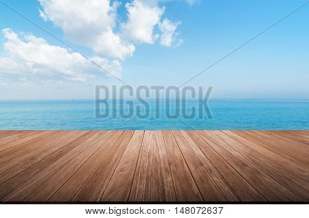 wood table top on blurred blue sea and sky