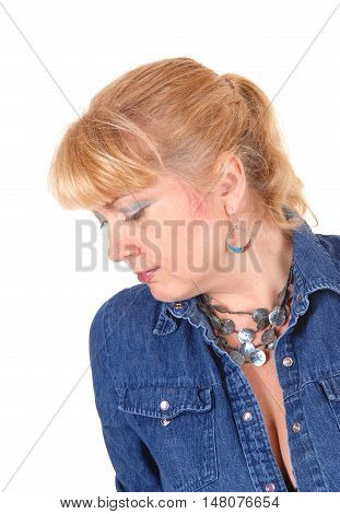 A portrait image of a pretty blond woman in a jeans jacket looking down isolated for white background.