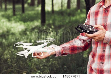 Unrecognizable man running drone with camera in forest. Review of new unmanned copter for filming and photographing outdoor. New tool for aerial photo and video