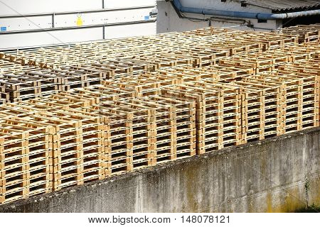 Stacked wooden pallets are in the backyard of a factory.