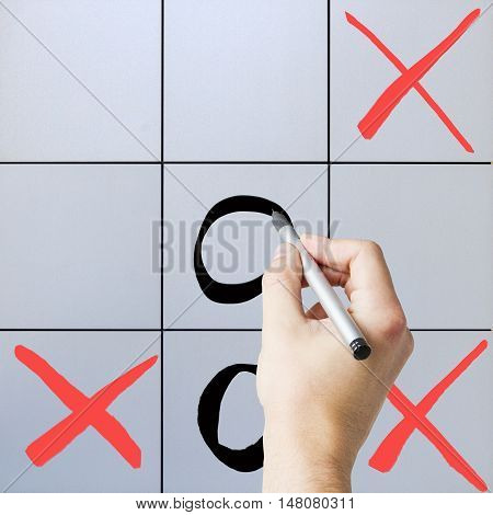 Male hand playing tic-tac-toe game on grey background
