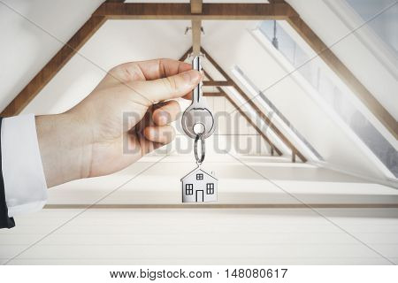 Hand holding key with house keychain on loft interior background. Real estate and mortgage concept