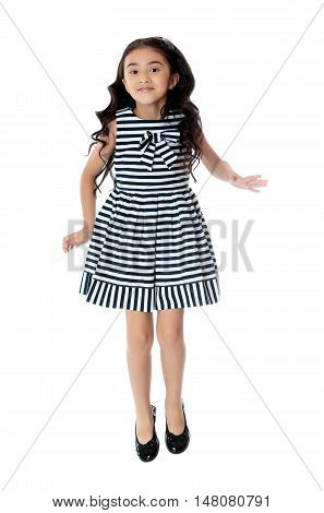 Joyful little girl of Eastern appearance in a dress . Long dark ponytails hair down below the shoulders. Girl jumping - Isolated on white background