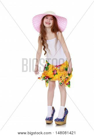 Nice little girl in a pink hat and a white tank top without a pattern . The girl wore on his feet shoes with high heels - Isolated on white background
