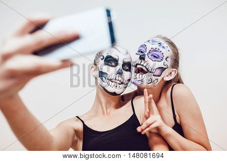 Two girls going on Halloween, grimace and make selfie