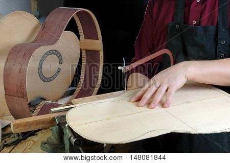 Luthier a fret saw to cut the upper deck of the classical guitar