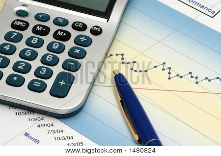 Close-Up Of Stock Report With Calculator And Blue Pen