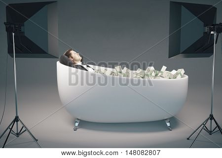 Young businessman relaxing in bathtub filled with dollar banknote stacks illuminated with professional lighting equipment on grey background. Success concept. 3D Rendering