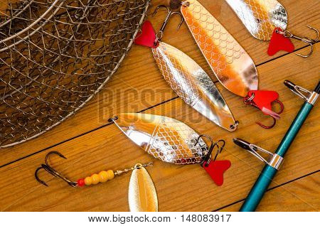 Fishing accessories for summer. Tackle bait lure jig hook net. Wooden background. Outdoor activity and leisure concept.