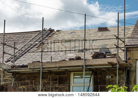 WREXHAM WALES UNITED KINGDOM - AUGUST 06 2016: Restoration of decorative slate roof on a residential terraced house in North Wales.