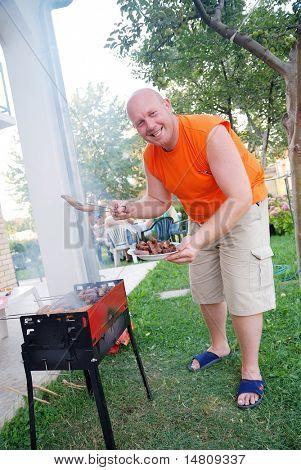 man preparing sausages on grill