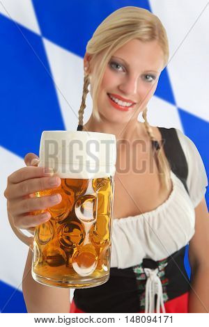 Bavarian Waitress with traditional clothing holding Oktoberfest Beer with a bavarian flag in the background
