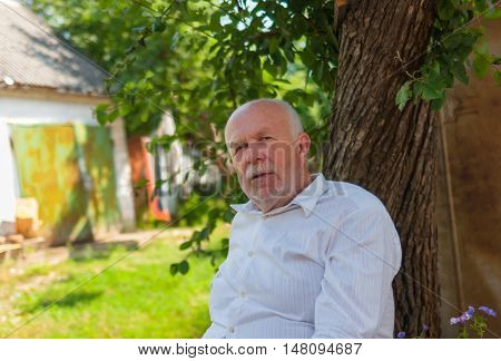 Portrait of Ukrainian elderly peasant sitting under tree shadow at summer season