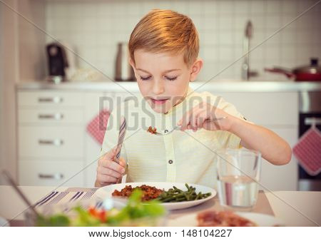 Young Diligent Boy  At A Table Eating Healthy Meal