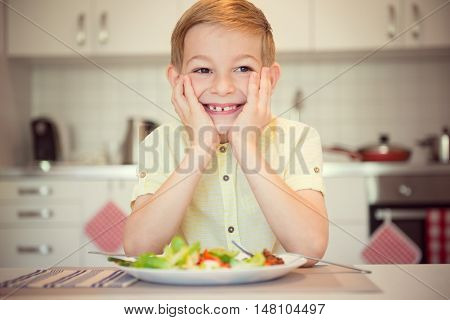 Young Diligent Happy Boy  At A Table Eating Healthy Meal