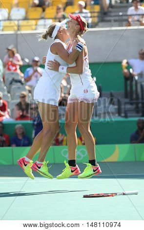 RIO DE JANEIRO, BRAZIL - AUGUST 14, 2016: Elena Vesnina (L) and Ekaterina Makarova of Russia celebrate victory after women's doubles final of the Rio 2016 Olympic Games at the Olympic Tennis Centre