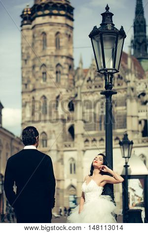Beautiful bride and handsome groom elegant fashion married couple in wedding dress and suit pose outdoors on streetscape background