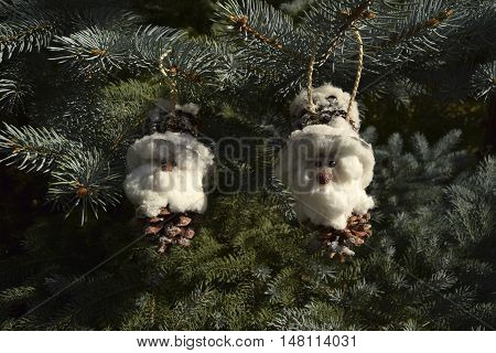 Christmas toys in the form of gnomes. Toys are located on a fir-tree. Gnomes are made of fir cones and cotton wool