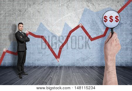 Businessman standing on the background of rising diagram with big man's hand enlarging dollar signs with a magnifier. Success and profit. Stock market. Shares go up.