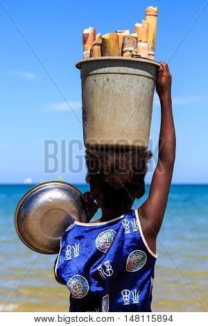 Young Girl Carrying A Heavy Bucket With Bamboo On Her Head