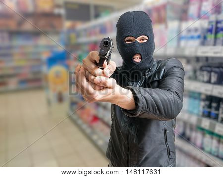 Robbery In Store. Robber Is Aiming And Threatening With Gun In S