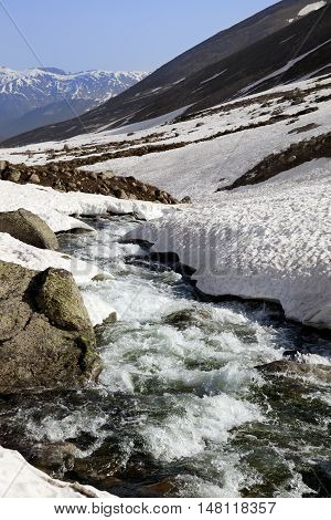 Mountain River With Snow Bridges In Spring Sun Day