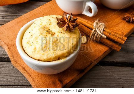 Pumpkin mug-cakes in rustic style, on an old wooden table, next to the cuted pumpkins and spices, close view, copy space