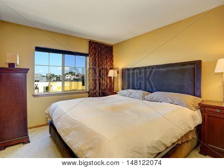 Bedroom Interior With King Size Bed And Brown Curtains.