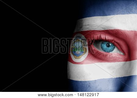 A young female with the flag of Costa Rica painted on her face on her way to a sporting event to show her support.