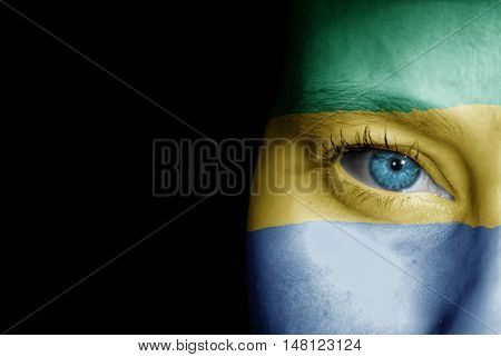 A young female with the flag of Gabon painted on her face on her way to a sporting event to show her support.