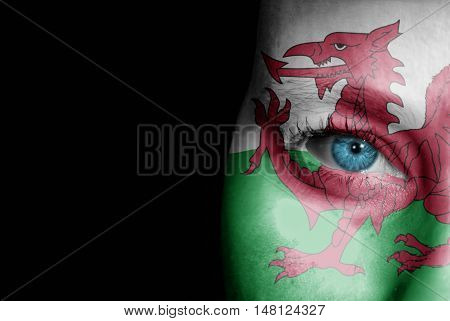 A young female with the flag of Wales painted on her face on her way to a sporting event to show her support.