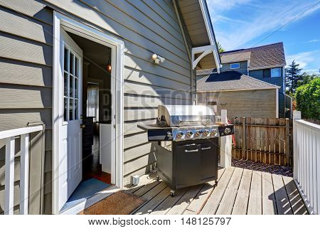 Wooden Walkout Deck With Barbecue. Blue Siding House