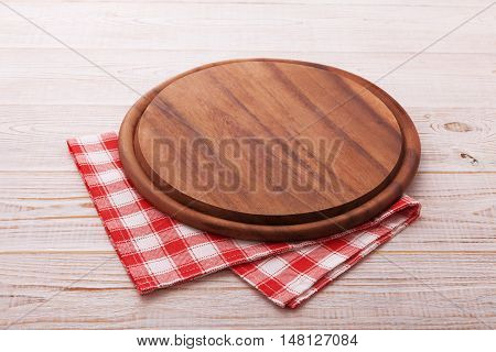 Pizza board with a napkin on white wooden table. Top view mock up
