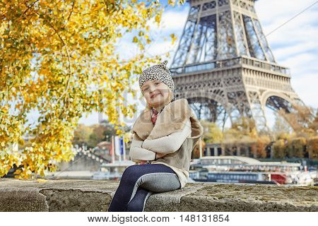 Elegant Child Sitting On Parapet On Embankment Near Eiffel Tower